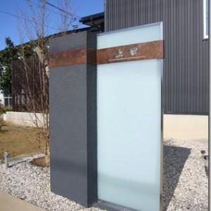 大型ガラスパネルに緑青サインを取り付けた門柱。