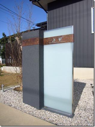 大型ガラスパネルに緑青サインの門柱