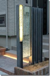 点灯したH鋼に取り付けられたリコストーン入りのガラスサイン。